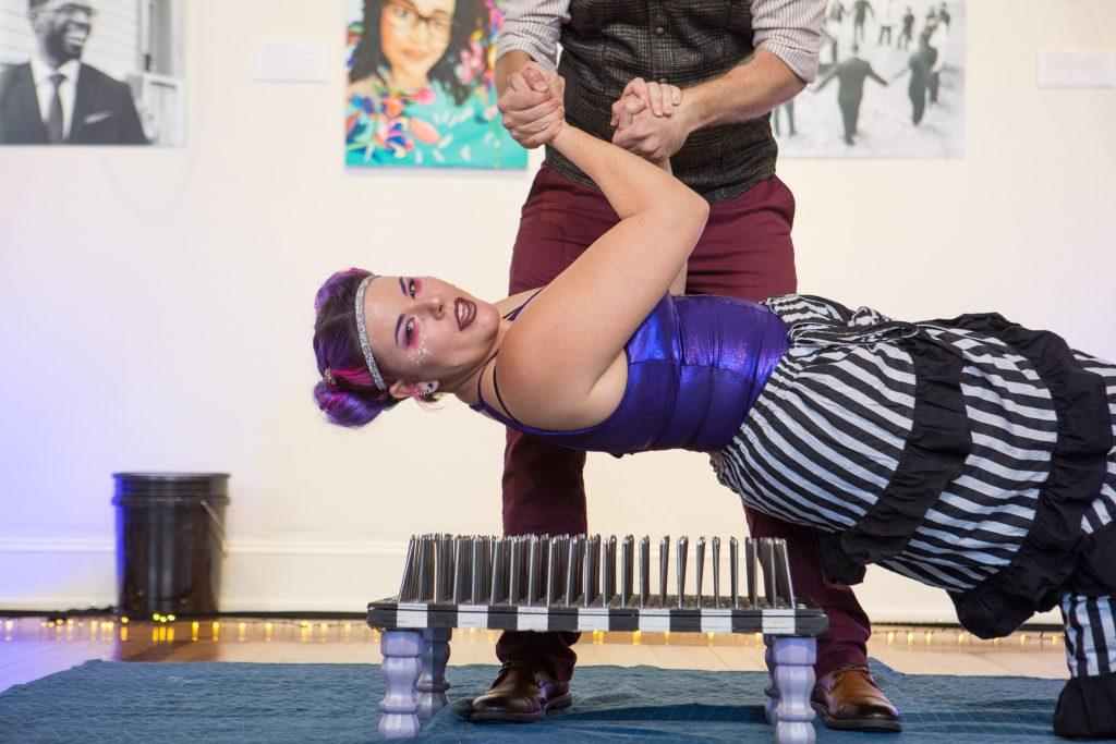 Sideshow artist Krystal Younglove laying on a bed of nails